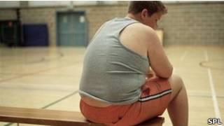Мальчик с излишним весом на скамейке