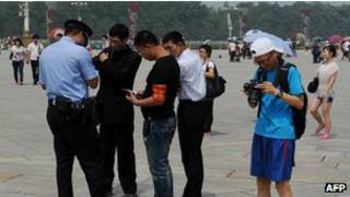 Policiais e transeuntes na Praça da Paz Celestial (AFP)