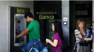 مواطنون إسبان أمام ماكينة صراف آلي