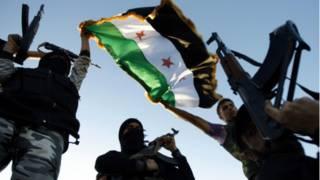 سوريون يستعرضون أسلحتهم بالقرب من إدلب