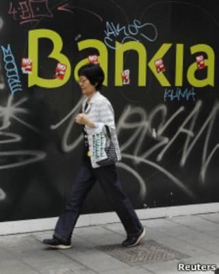 Mulher passa em frente a fachada do Bankia, nacionalizado pelo governo espanhol