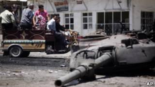 Sírios olham para tanque destruído na região de Idlib. Foto AP