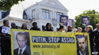 صورتان للأسد وبوتين، وشعار يقول: أوقف الأسد يا بوتين