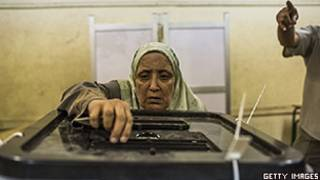 Mulher egípcia deposita voto em urna no Cairo (Getty)