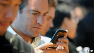 Homem usando smartphone (Foto AFP)