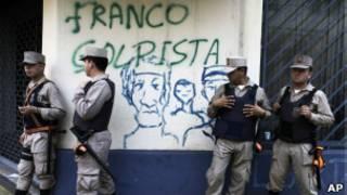 Policiais paraguaios em frebte a pixação contra Franco em Assunção