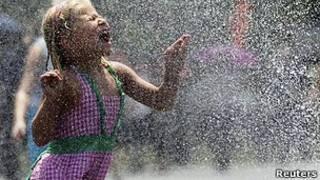 کودکی که با آب بازی تلاش می کند خود را خنک کند