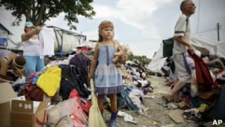 Девочка с веником и игрушкой посреди вещей в Крымске