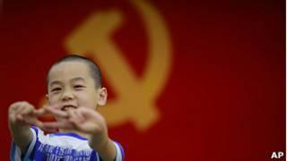 Garoto em frente à bandeira da China | Crédito da foto: AP