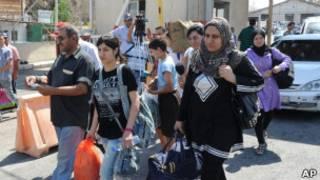 Sírios cruzam fronteira com o Líbano (foto: Associated Press)