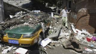 Moradora de Pequim tenta desviar de destroços deixados pela enchente (Reuters)