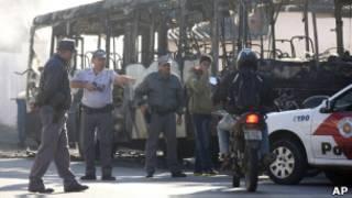 Policiais abordam motoqueiro após ataque a ônibus (foto: Associate Press)