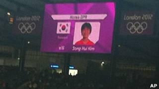 Bandera de Corea del Sur al lado de una jugadora de Corea del Norte