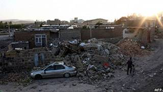 Homem e criança passam por casas destruídas na cidade de Varzaqan, 60 km a leste de Tabriz, também atingida por terremoto (AFP/Getty)