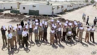 """Члены """"Моджахеддин-э Хальк"""" с плакатами в лагере беженцев в Ираке (11 сентября 2012 года)"""
