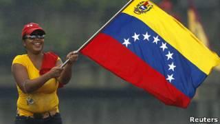 Seguidora de Chávez ondea una bandera venezolana