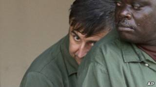 Александр Фишенко прячет лицо за плечом другого заключенного