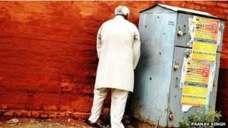 Hombre orinando en público en India.