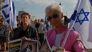 Женщины с лозунгами в адрес Обамы и флагами Израиля
