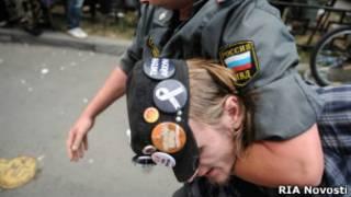 Полицейский задерживает активиста