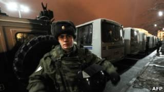 Полицейский на фоне автозаков