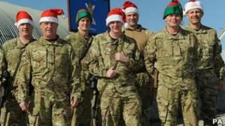 Солдаты в хаки и колпаках Санта-Клауса