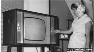 Mujer enciende aparato de TV (foto de archivo)