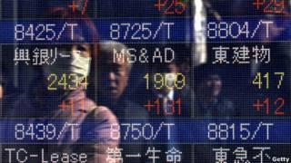 Chinos observan un tablero electrónico con índices económicos.