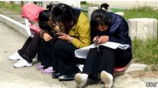 Северокорейцы с мобильными телефонами