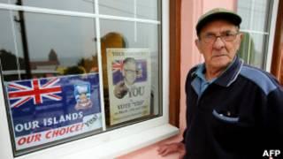 Eleitor passa ao lado de propaganda durante pleito nas Malvinas (foto: AFP)