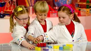 Две девочки и мальчик играют в кубики