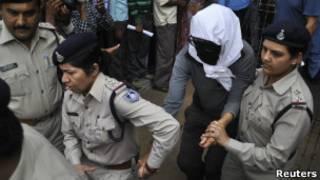 Turista suíça, coberta, é acompanhada por policiais após prestar depoimento