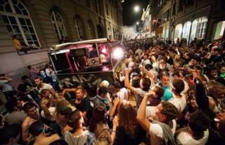 جوانان خوشگذران در جشنی خیابانی در حال رقص در شهر برن