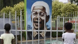 Crianças olham para retrato de Mandela em m parque em Soweto (foto: AP)
