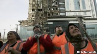Рабочие у сгоревшего комплекса в Грозном