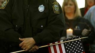 Boston Maratonu sonrasında güvenlik görevlisi elinde bayrak tutuyor