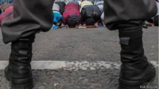 Молящиеся мусульмане и полицейский