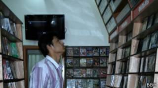 Покупатель в магазине рассматривает полки с DVD