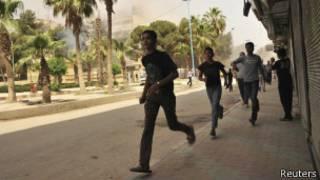 Jovens procuram abrigo durante ataque a Raqqa, no leste da Síria (foto: Reuters)