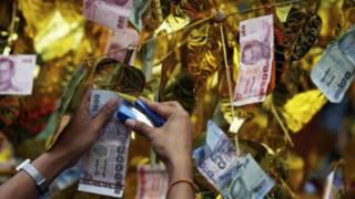 Phật tử cài tiền lên cây nhân ngày Phật Đản taiij Thái Lan. Ảnh: Reuters/Damir Sagolj.