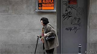 Mulher em Madri passa em frente a imóvel fechado (Reuters)