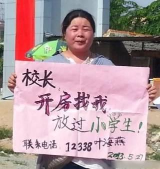 """叶海燕举着""""校长开房找我""""标语牌的照片(网络照片)"""