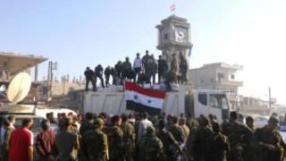 Quân chính phủ ăn mừng ở tháp đồng hồ ở trung tâm Qusair