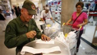 Солдат проверяет чеки в супермаркете в Каракасе