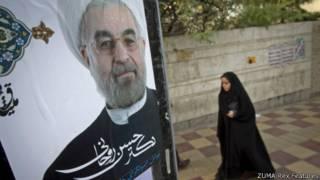 一名伊朗婦女走過掛有魯哈尼競選的宣傳牌(12/06/2013)