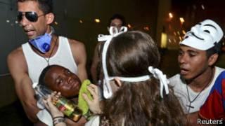 Manifestantes socorrem jovem afetado por gás lacrimogêneo em Salvador (foto: Reuters)