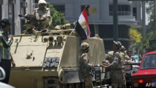 Soldados egípcios próximos a um veículo blindado no caminho da Universidade do Cairo, onde a Irmandade Muçulmana e o presidente Morsi estariam (AFP)