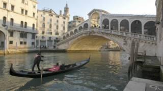 Gondoleiro na Ponte do Rialto, em Veneza | Foto: BBC