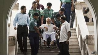 Azam, en silla de ruedas, ayudado por personal de seguridad en el tribunal