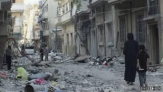 Pessoas caminham pela devastada cidade de Homs